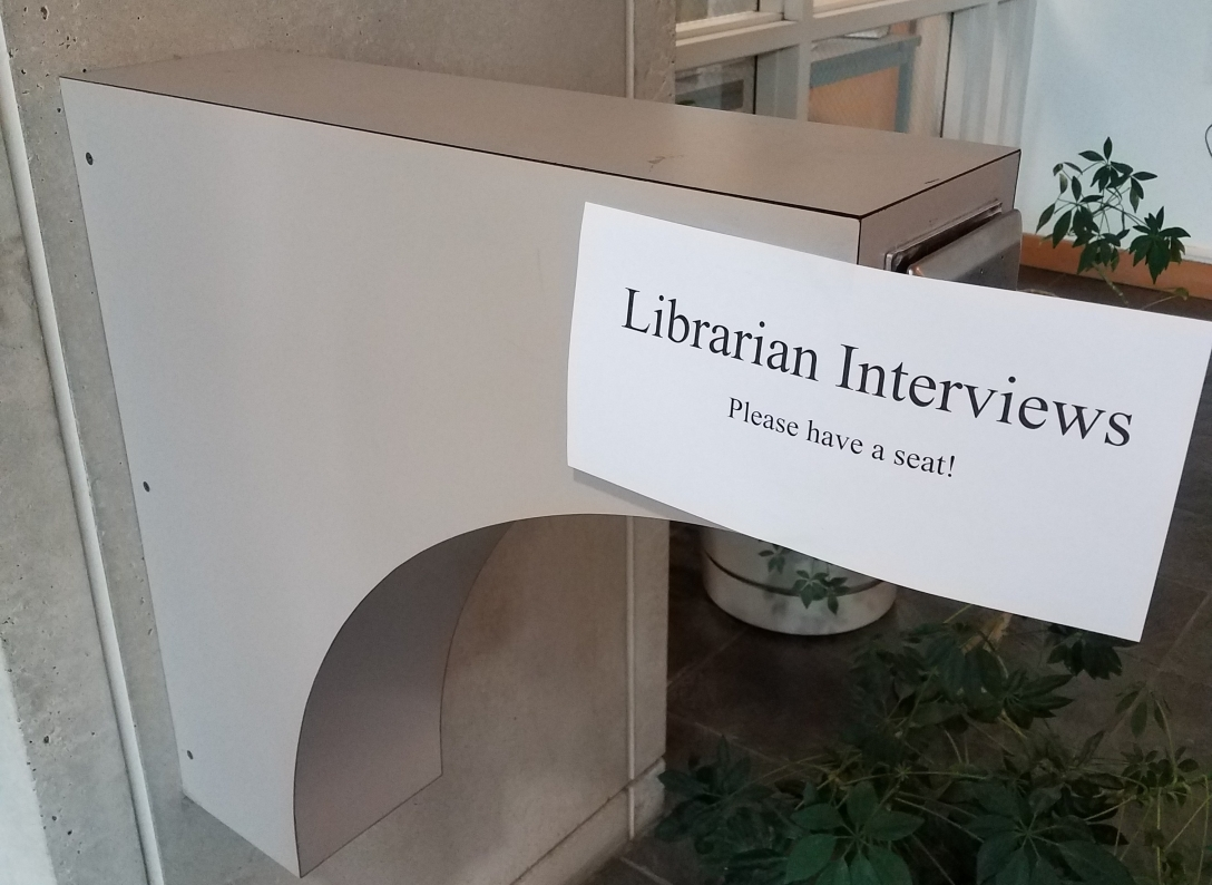 typed sign that says Librarian Interviews: Please have a seat