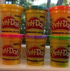 six containers of play-doh in different colors